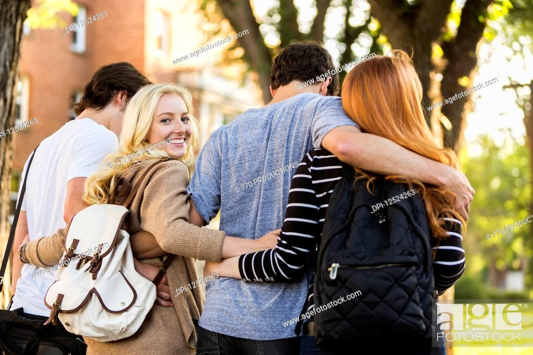Stock Photo: Four friends walking and talking in an embrace on the university campus with a female looking back at the camera; Edmonton, Alberta, Canada.