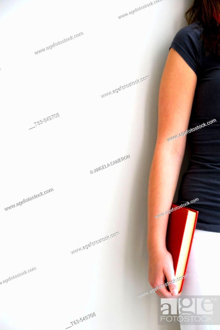 Stock Photo: girl/woman 20 yrs old standing against wall holding red book.
