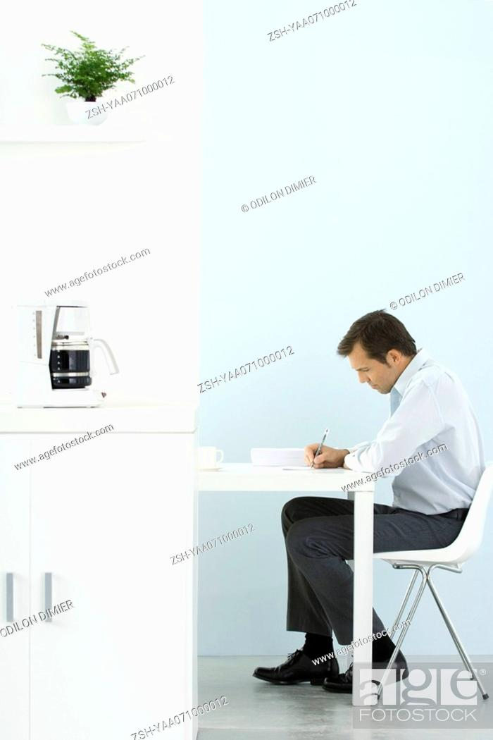 Stock Photo: Man sitting at desk, working, coffee maker on counter in foreground.
