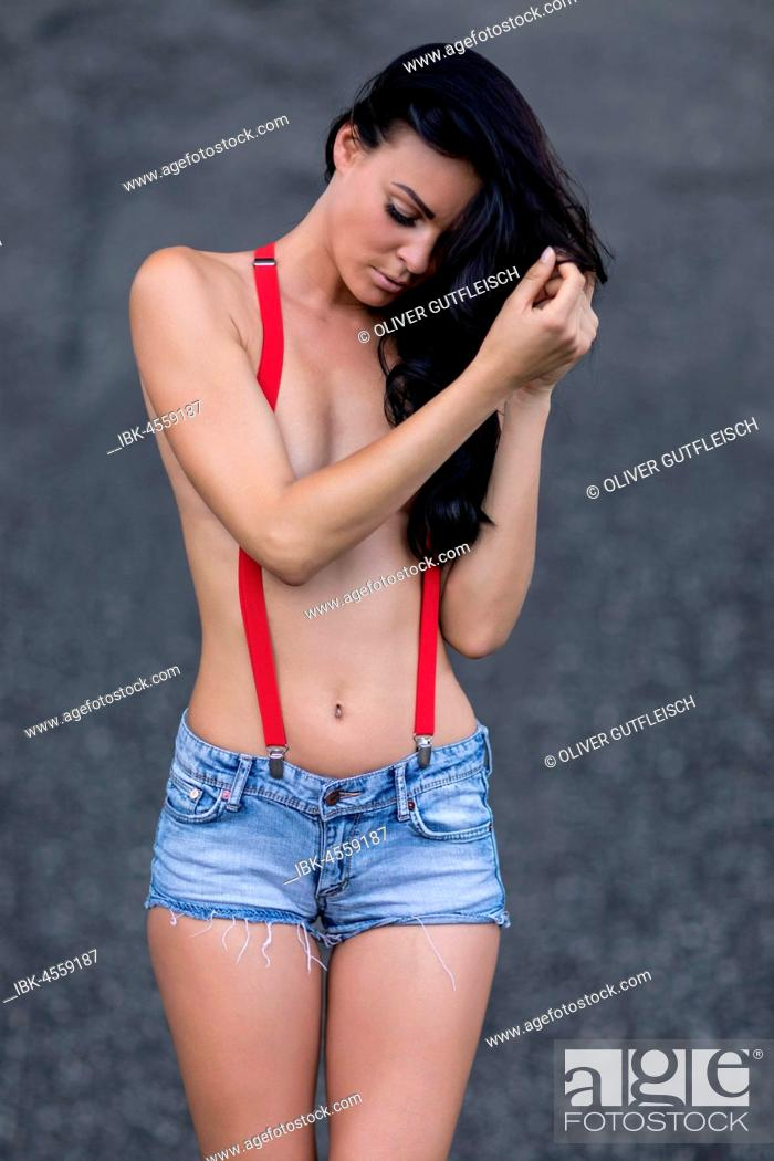 Stock Photo: Woman with jeans hotpants and red suspenders.
