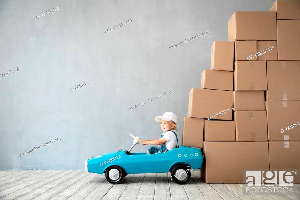 Stock Photo: Happy child playing into new home. Kid driving toy car. Moving day concept.