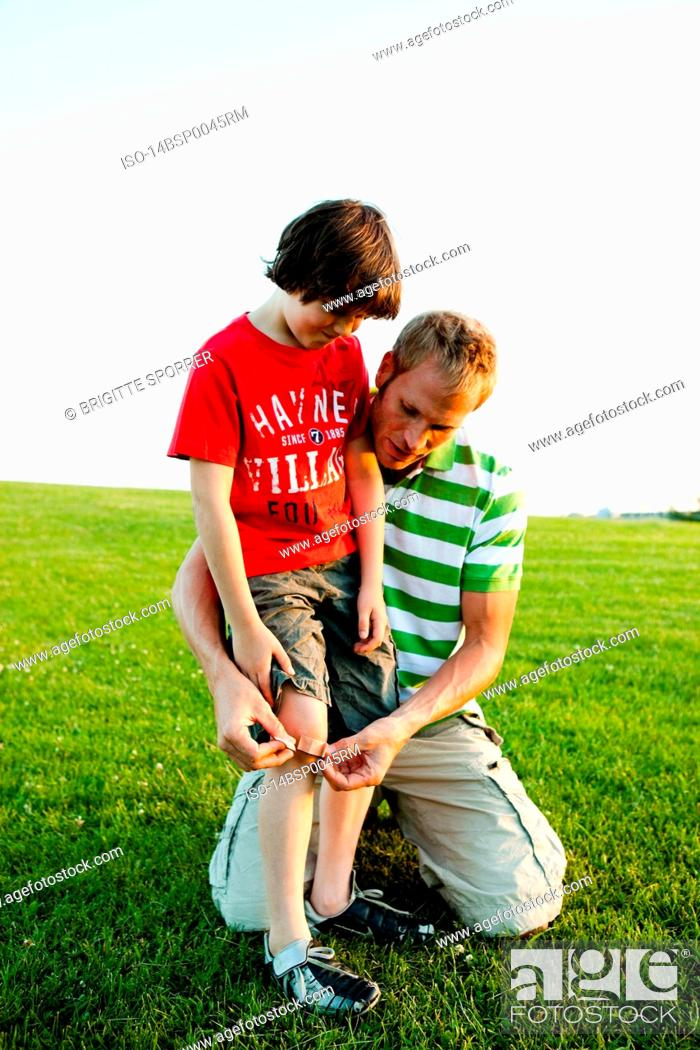 Stock Photo: Father Applying Bandage to Son's Knee.