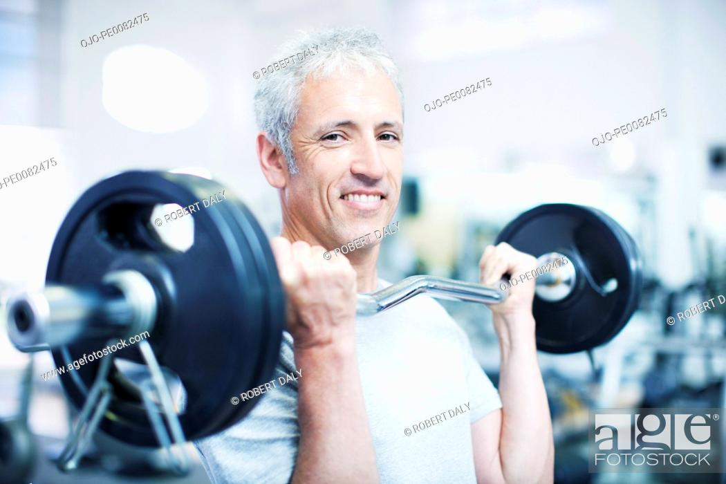 Stock Photo: Portrait of smiling man holding barbell in gymnasium.