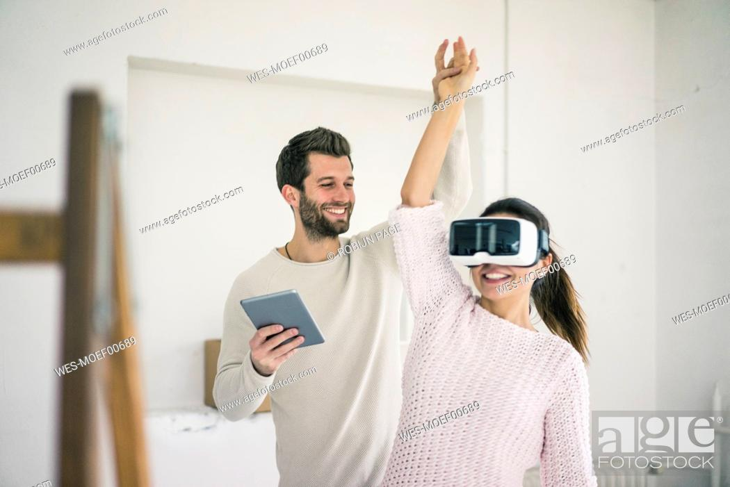 Stock Photo: Man lifting woman's arm wearing VR glasses in new home.