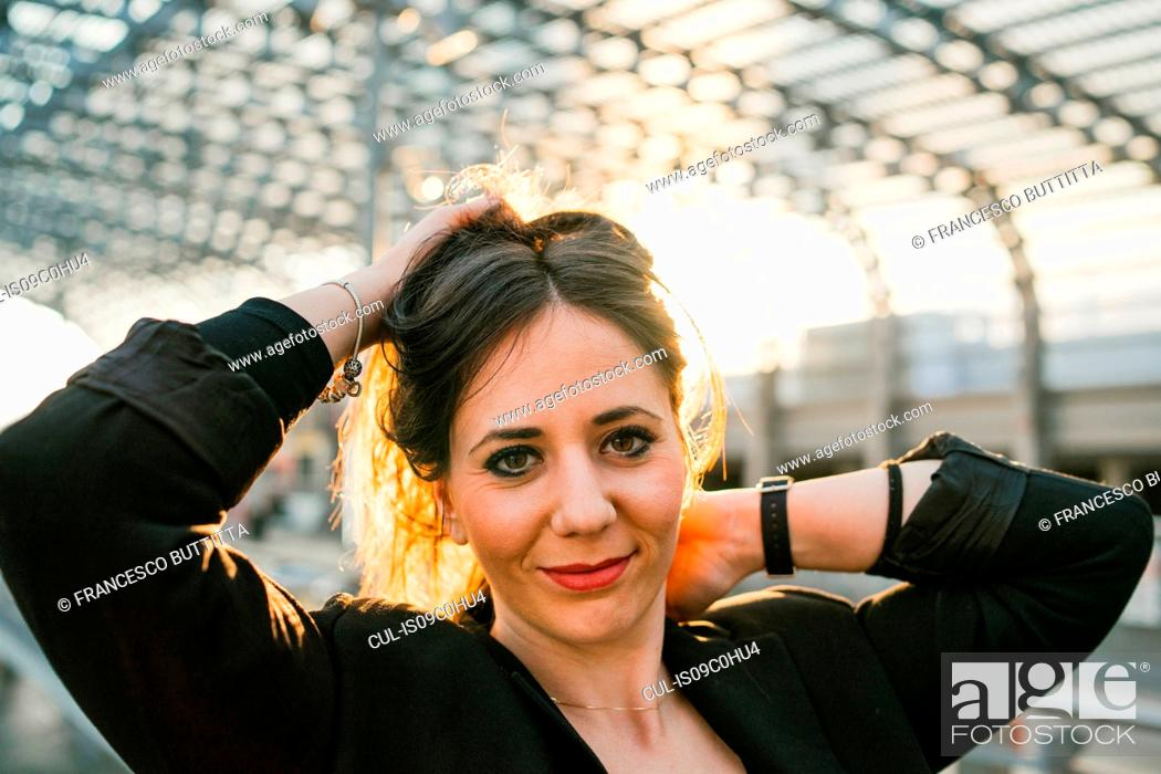 Stock Photo: Young woman with hands in hair in train station, portrait, Turin, Piemonte, Italy.