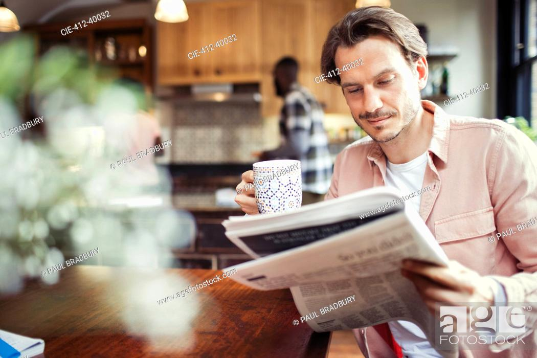 Stock Photo: Man drinking coffee and reading newspaper in kitchen.