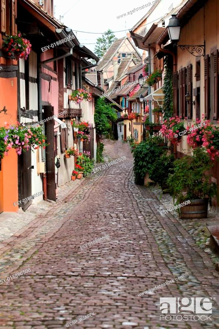 Stock Photo: Street with half-timbered medieval houses in Eguisheim village along the famous wine route in Alsace, France.