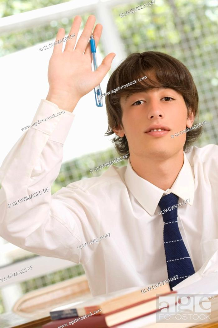 Stock Photo: Portrait of a young man raising his hand in a classroom.