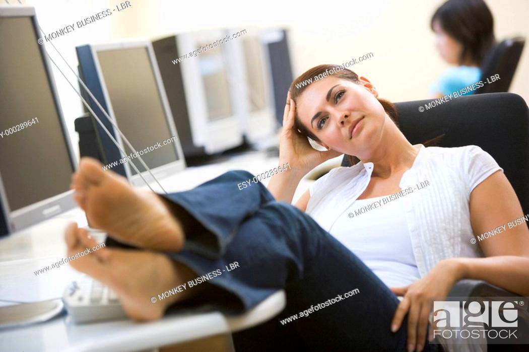 Stock Photo: Woman in computer room with feet up thinking.