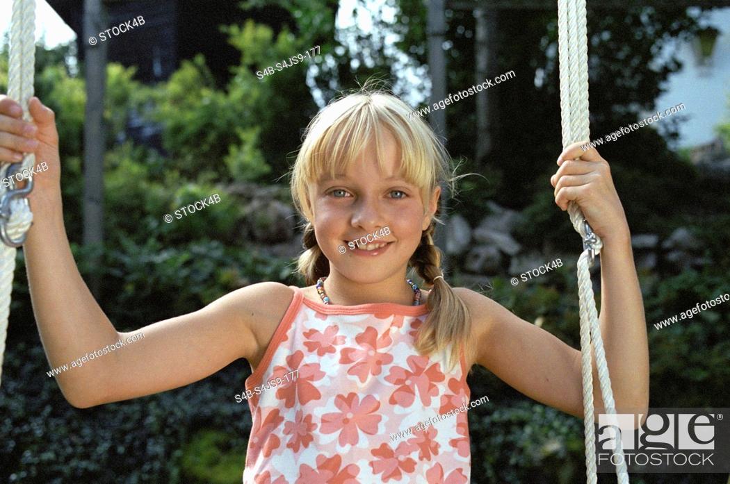 Stock Photo: Blonde Girl sitting on Swing - Garden - Summer.