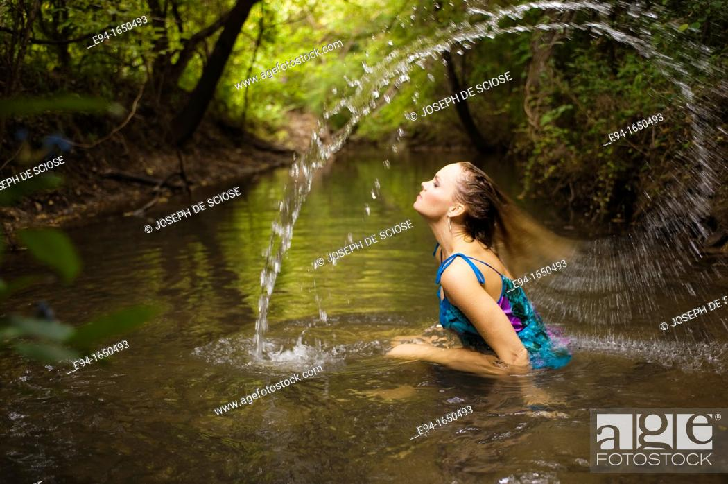 Stock Photo: 34 year old blond woman in a flower print dress sitting in the water of a small creek swooshing her hair in a water arc over her head.