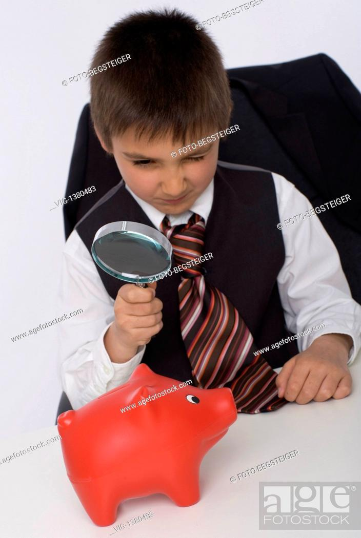 Stock Photo: little businesman watching piggy bank under loupe - 30/04/2009.
