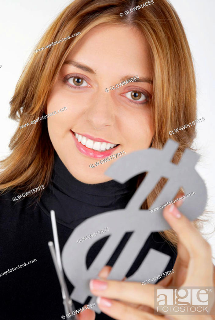 Stock Photo: Portrait of a businesswoman holding a dollar sign with a pair of scissors and smiling.