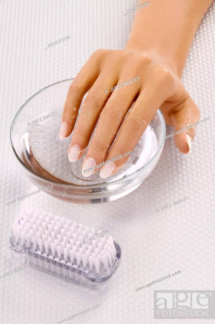 Stock Photo: Close up of woman's hand in bowl of water next to nail brush.