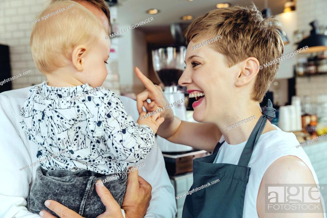 Stock Photo: Waitress playing with baby of customer in cafe.