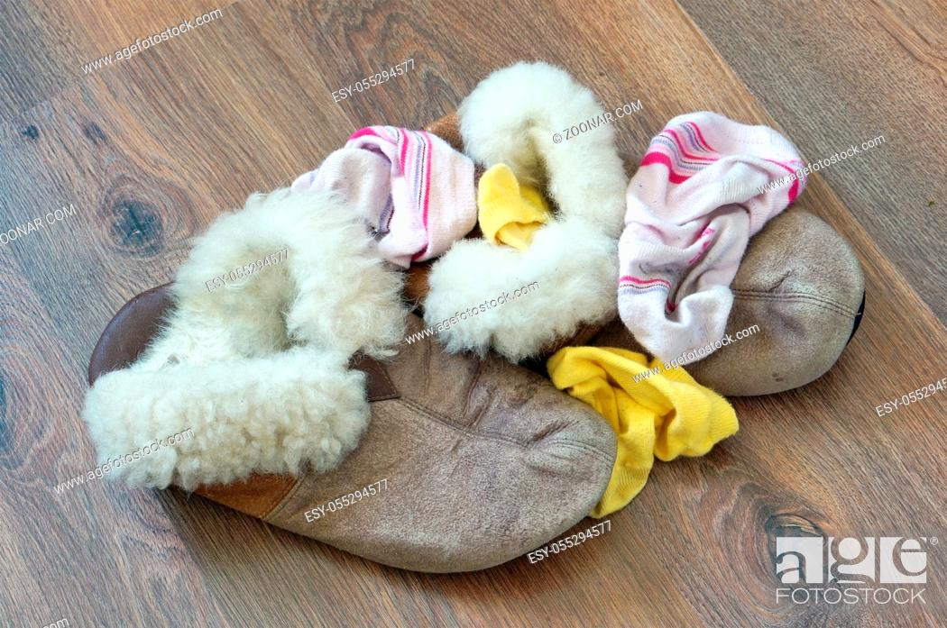 Stock Photo: Old fur women's house slippers and socks lie a bunch on the wooden floor.