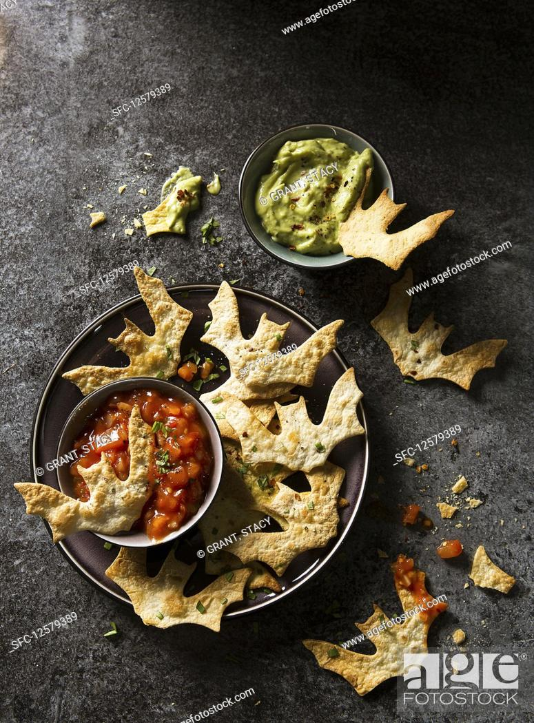 Stock Photo: Halloween bat torilla chips with tomato and guacamole dip.