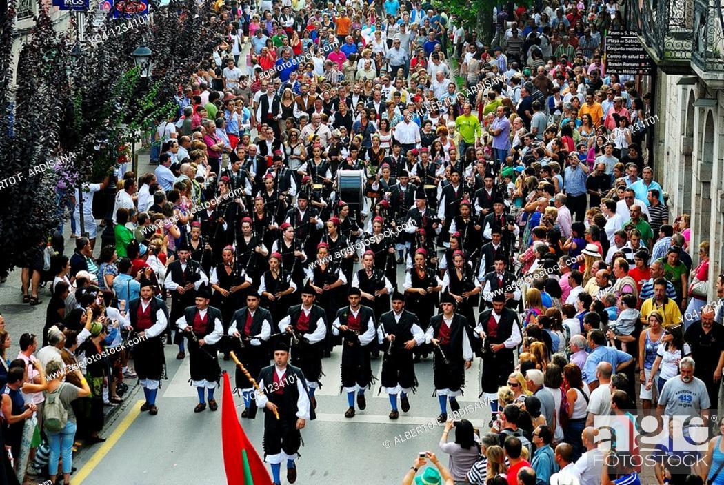 Stock Photo: Llacín pipe band marching through the streets of Llanes, Asturias Fiestas de San Roque.