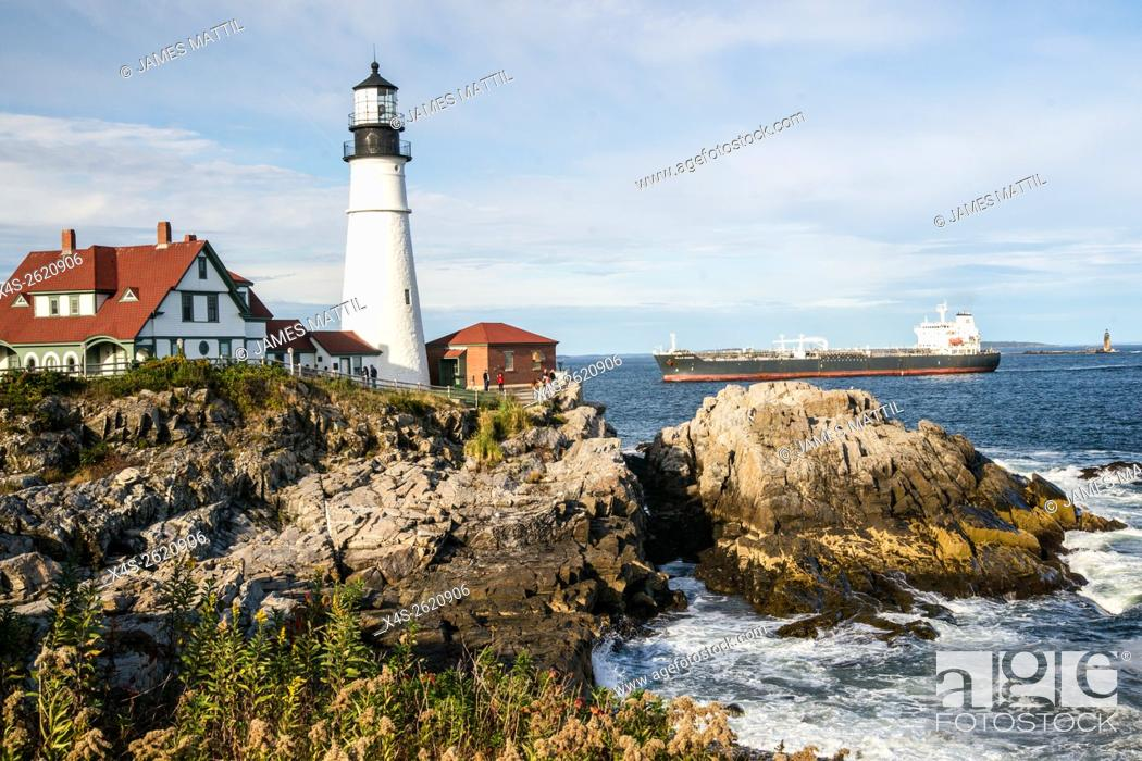 Stock Photo: View of the landmark Portland head lighthouse in Maine as a ocean freighter approaches.
