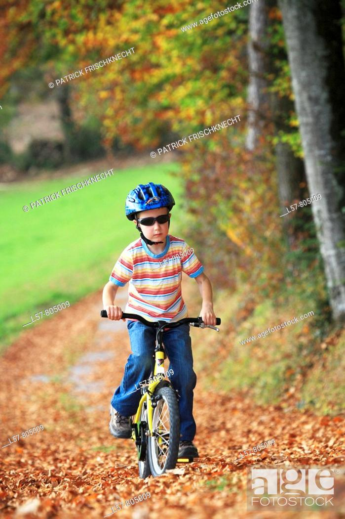 Stock Photo: boy riding his bicycle on road with leaves in fall, autumn foliage covering path in forest, autumn, fall, Zuerich, Switzerland.