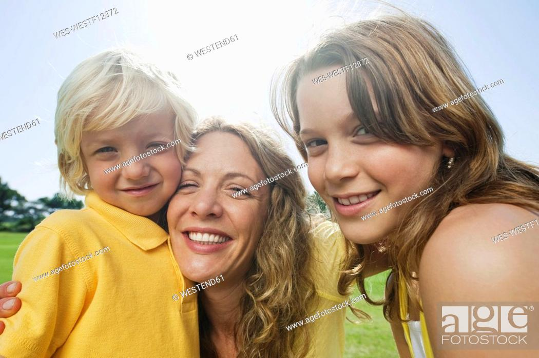 Stock Photo: Spain, Mallorca, Mother with children 4-5, 10-11, smiling, portrait, close-up.