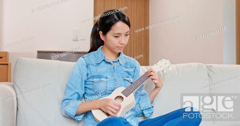 Imagen: Woman enjoy play with ukulele.