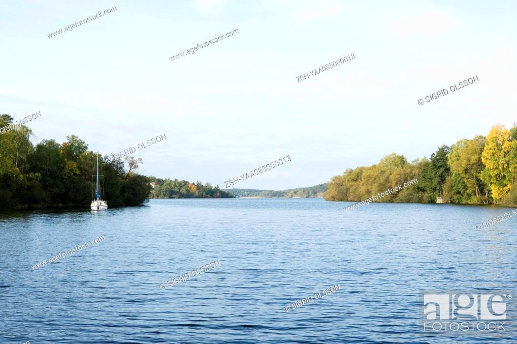 Stock Photo: Lake with sail boat and trees in distance.