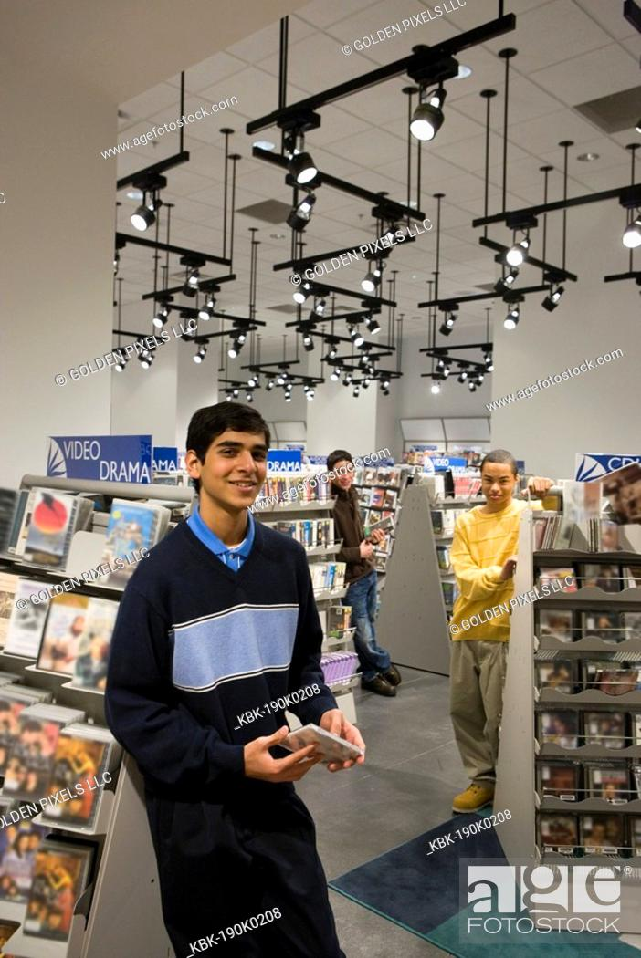 Imagen: Portrait of smiling teenage boys standing amidst shelves of DVDs.