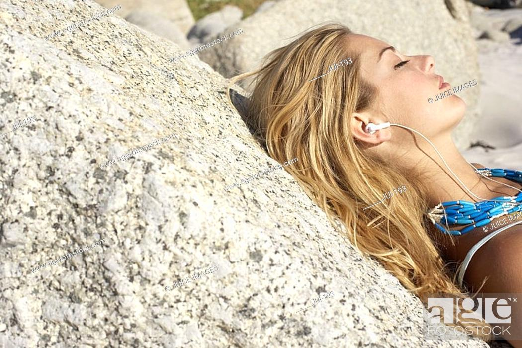 Stock Photo: Blonde teenage girl 17-19 relaxing on beach, leaning against rock, eyes closed, side view.