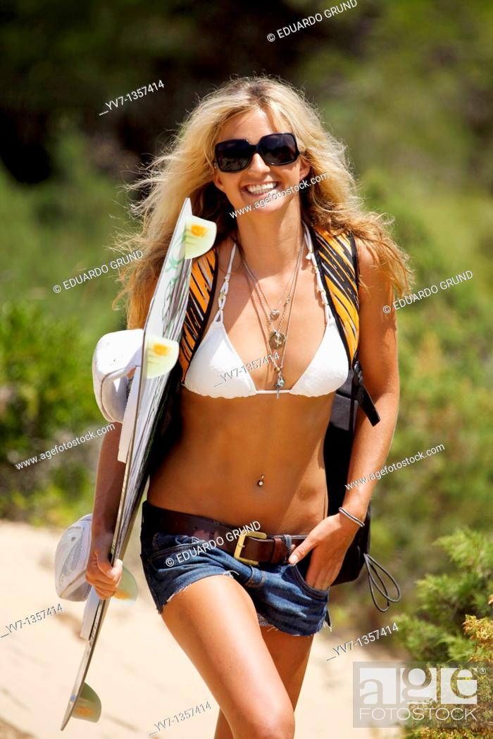 Stock Photo: Smiling young blonde woman with a kitesurf board and a sunglasses.
