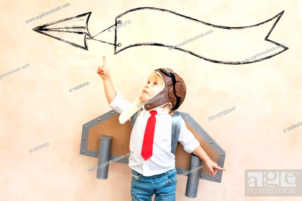 Stock Photo: Funny kid with toy jet pack. Happy child playing at home. Success, imagination and innovation technology concept.