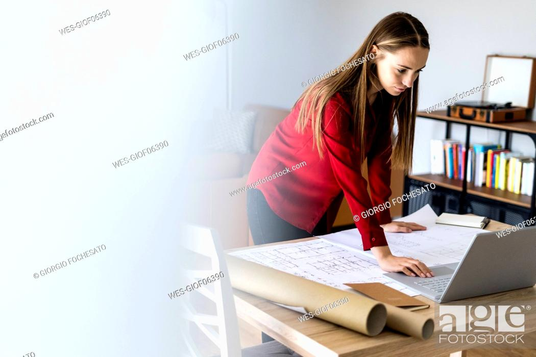Stock Photo: Woman in office working on plan and laptop on table.