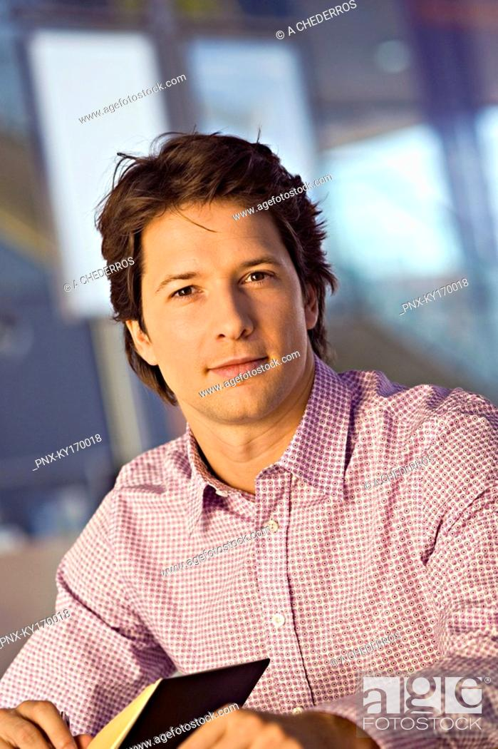 Stock Photo: Portrait of a businessman holding a diary.