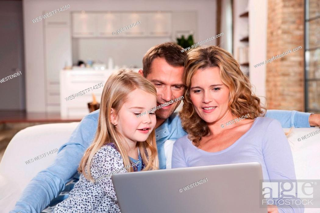 Stock Photo: Germany, Cologne, Family on sofa using laptop, portrait.
