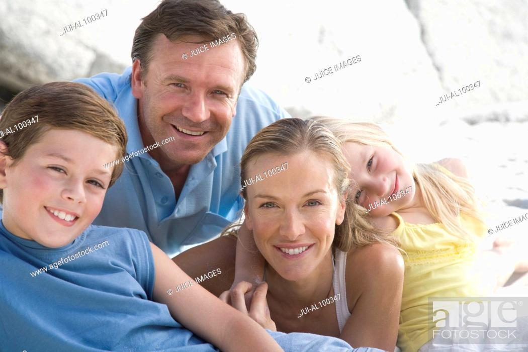 Stock Photo: Family sitting on beach.