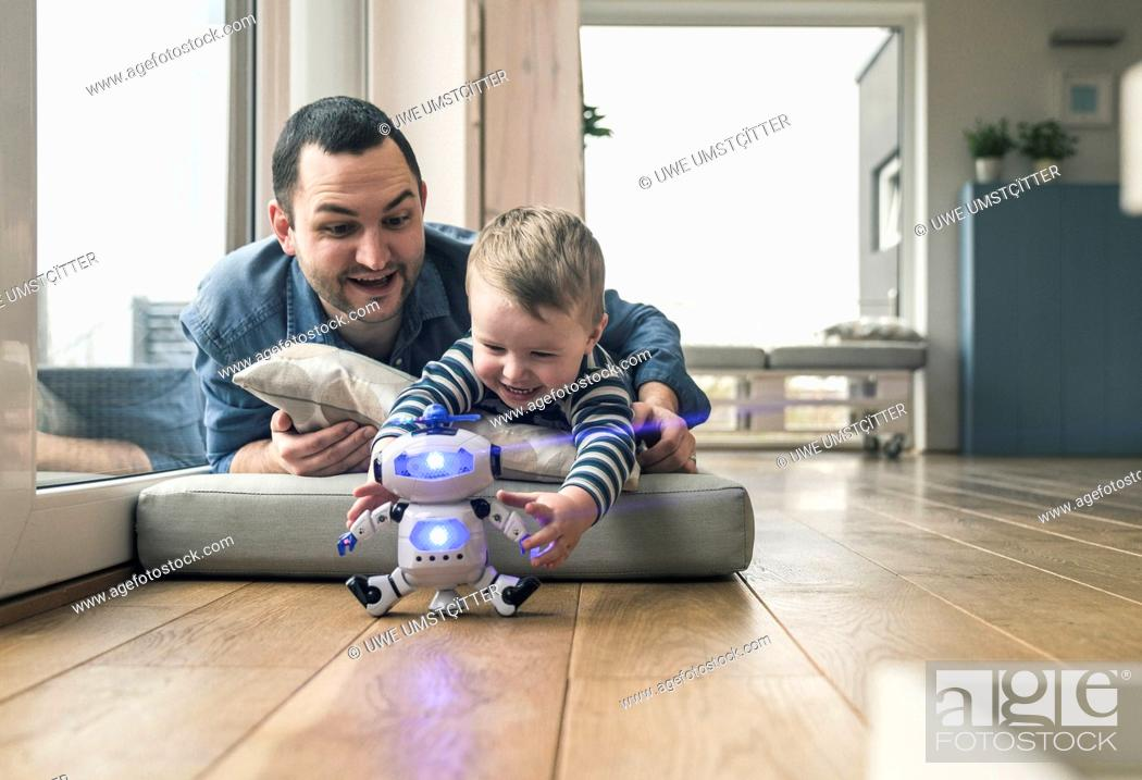 Stock Photo: Excited father and son lying on a mattress at home playing with a toy robot.