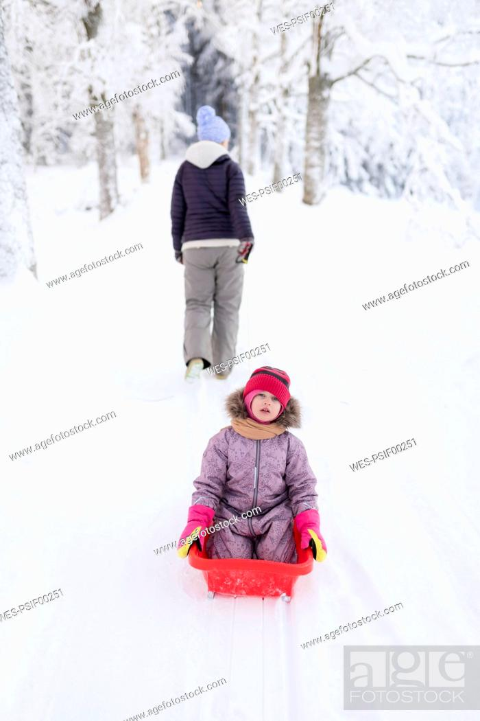 Stock Photo: Finland, Kuopio, mother and daughter sledging.