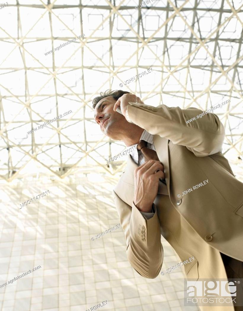 Stock Photo: Businessman using mobile phone outdoors low angle view.
