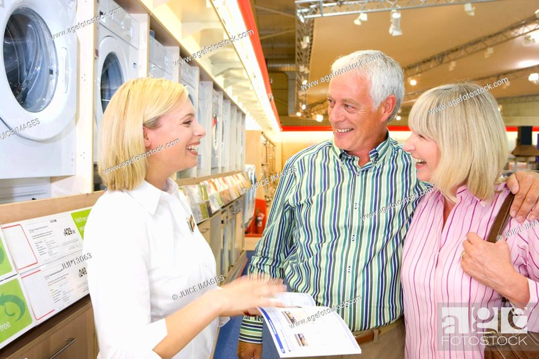 Stock Photo: Mature couple in appliance shop smiling at shop assistant with brochure.
