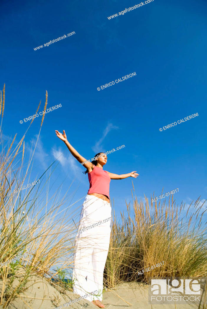 Stock Photo: Young woman exercising on sand dune.