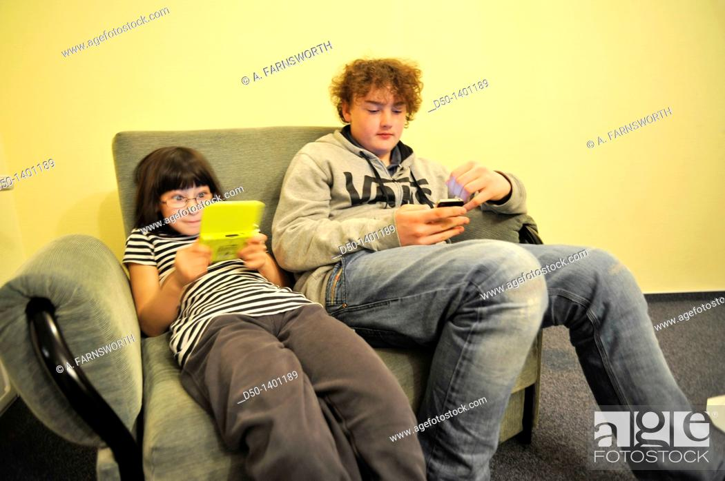 Stock Photo: Swedish 10 and 14 year old playing games on their Nintendo and iPhone in hotel, Zakopane, Poland.