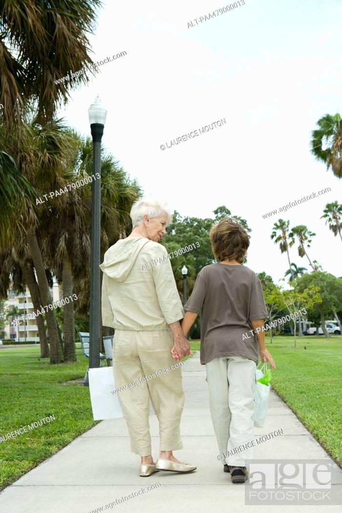 Stock Photo: Boy and grandmother walking on sidewalk, carrying shopping bags, talking, rear view.