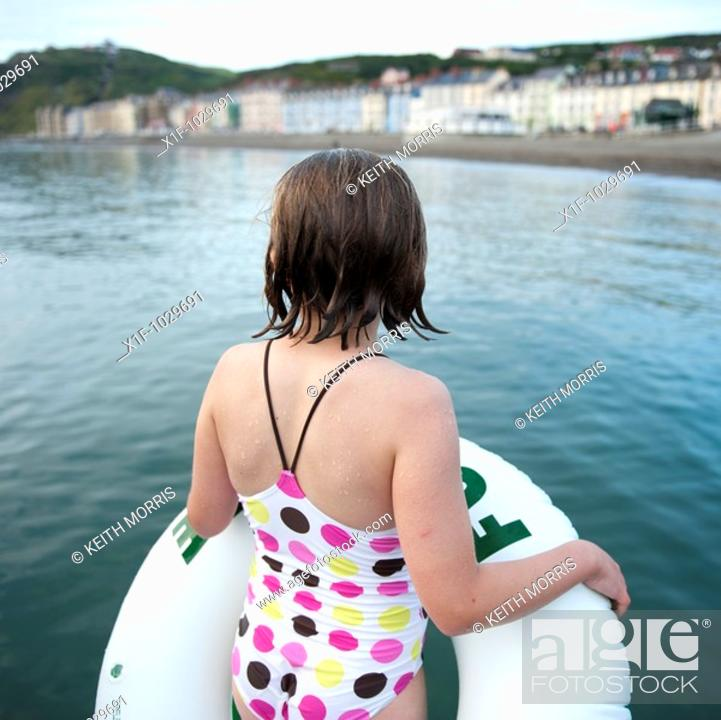 Stock Photo: Rear view of a ten year old gilr holding her rubber ring about to go swimming in the sea, summer evening.