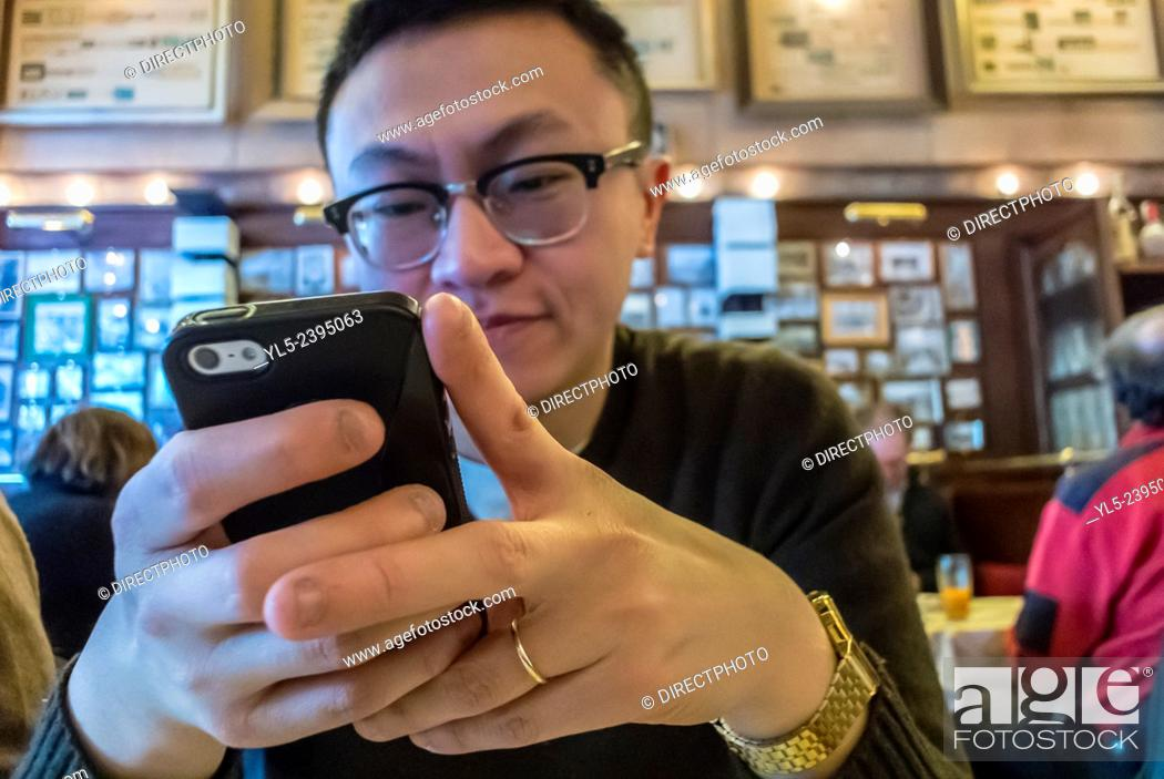 """Stock Photo: Berlin, Germany, Chinese Tourist Inside, German Cusine Restaurant, """"""""Joseph Roth Diele"""""""", Sending Text Message Holding Iphone, Smart Phone at Table."""