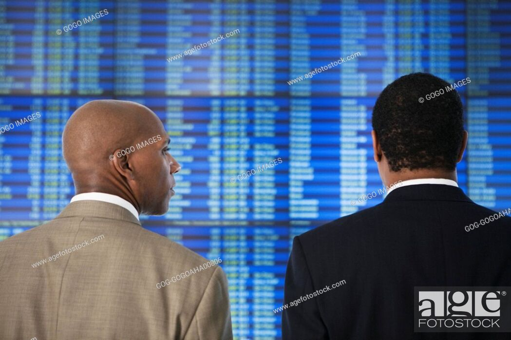 Stock Photo: African businessmen in front of Arrival Departure board.