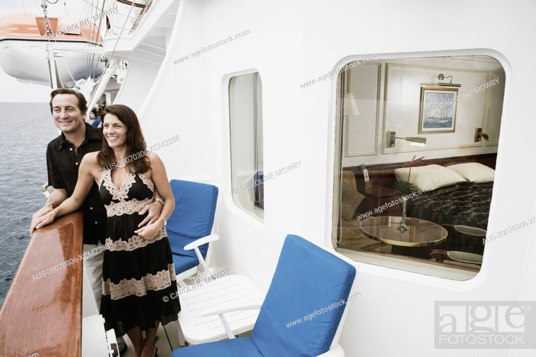 Stock Photo: Mid adult couple standing at the railing of a sailing ship and smiling.