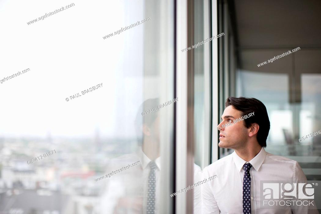 Stock Photo: Businessman looking out office window.