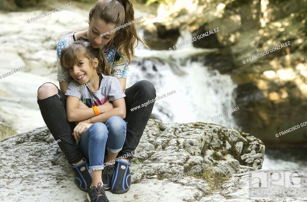 Photo de stock: Sisters sitting on rocks next to a river in the Seva de Irati de Navarra; Spain.