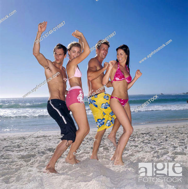 Stock Photo: Side profile of two young couples dancing on the beach.