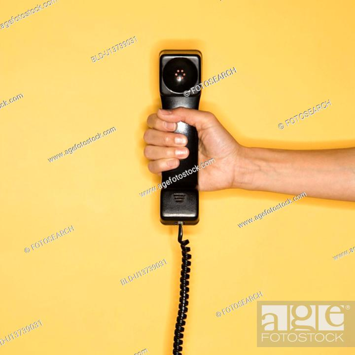 Stock Photo: Close up of woman holding telephone receiver on yellow background.